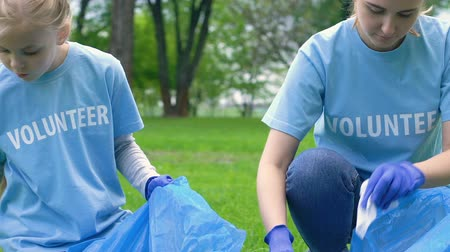 preservation : Woman and female child volunteers collecting trash in city park social eco event