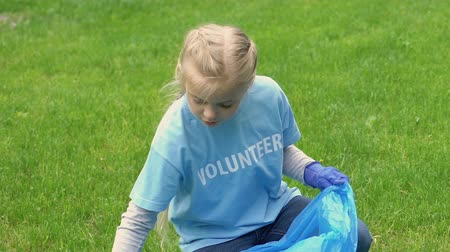 preservation : Responsible kid volunteer collecting rubbish in park, environmental activism