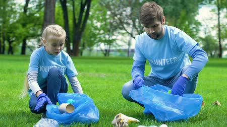preservation : Kid and father eco-volunteers collecting rubbish in park, social eco event Stock Footage