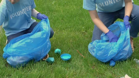 preservation : Two volunteers picking litter on lawn in park, ecology and environment concept