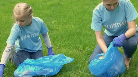 ekosistem : Mother and little girl volunteers collecting trash in park, giving high-five