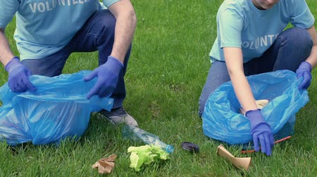 ekosistem : Volunteers picking litter on lawn ecology and environmental preservation concept