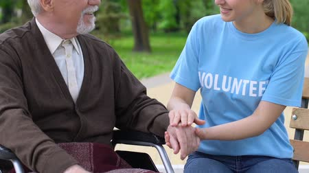 пенсионер : Sincere girl volunteer holding disabled retiree hand, supporting hospice people
