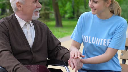 pomocník : Smiling young volunteer supporting elderly disabled man in park, helping retiree