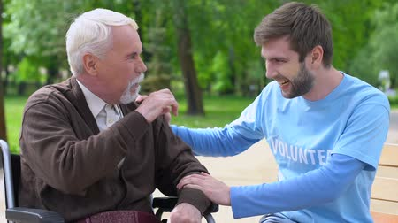philanthropy : Male volunteer and elderly disabled man laughing in park, lonely pensioners care