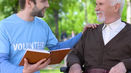 důchodce : Kind male volunteer reading book to smiling old man in wheelchair, assistance