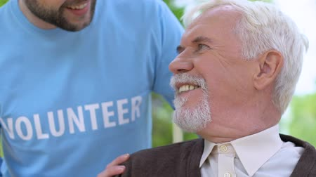 пенсионер : Caring male volunteer talking to aged lonely man during walk in park, assistance