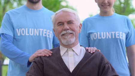 philanthropy : Smiling volunteers standing behind old disabled person, social support, charity Stock Footage