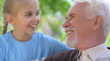 volontariat : Little girl volunteer talking to lonely aged man during park walk, retiree care Vidéos Libres De Droits