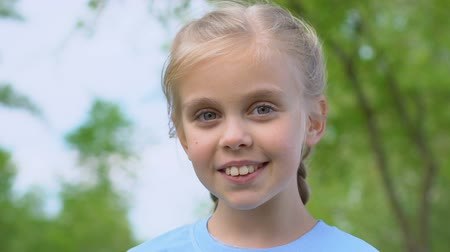 megőriz : Cute female kid sincerely smiling on camera, standing in park, joyful childhood