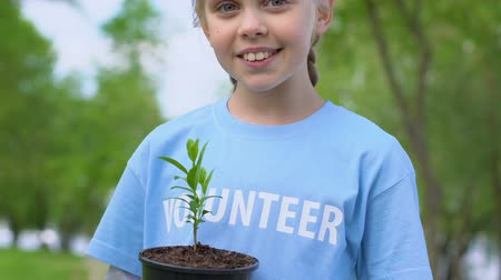 ekosistem : Pretty little girl holding plant sapling and smiling on camera, eco volunteering