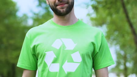 megőriz : Proud male in green t-shirt with recycling symbol smiling on camera, ecology