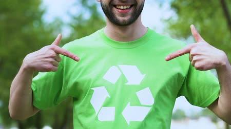 preservation : Smiling male eco-activist pointing finger on recycling symbol print on t-shirt