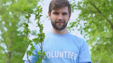 ekosistem : Smiling man volunteer holding tree sapling deforestation problem solving, nature