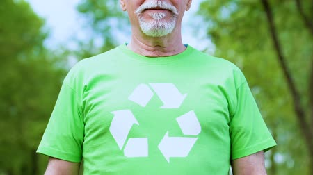 preservation : Senior male in recycling symbol t-shirt posing camera environmental volunteering Stock Footage