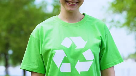 utilizzo : Kind woman in green t-shirt with recycling symbol, environmental volunteering