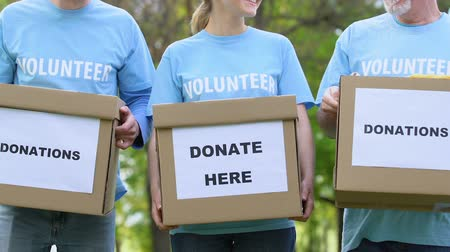 voluntário : Kind volunteers holding donation boxes and smiling, social charity project, help