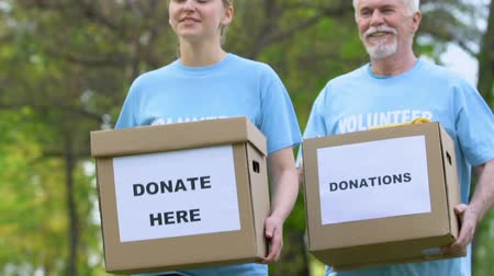 voluntary : Aged and young volunteers walking in park with donation boxes, humanity and help
