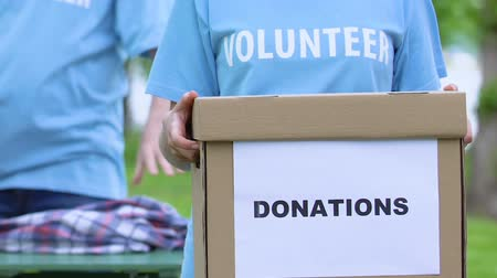 humanitarian : Female volunteer holding donation box, people sorting clothes, humanitarian aid