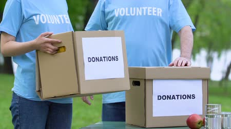voluntário : Two volunteers holding donation box, humanitarian mission, charity concept, help