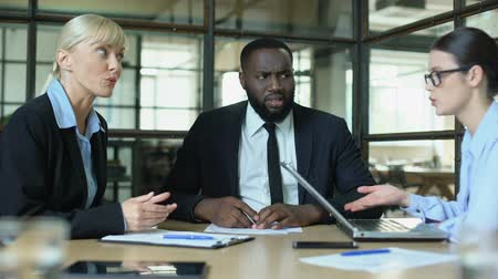 confronto : Black man showing no idea gesture listening to screaming female colleagues Stock Footage