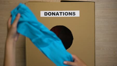 escrito : Woman putting used clothing in cardboard box for donations, charity organization