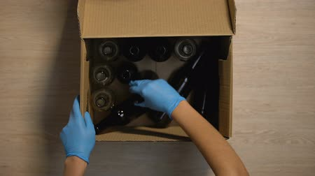 reutilizável : Volunteer in gloves accepting box with glass bottles, disposing reusable trash