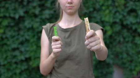 prendedor de roupa : Woman demonstrating wooden clothespin preferring it to plastic harmless material