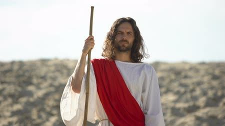 biblia : Jesus with wooden staff standing in desert, preaching Christian faith conversion