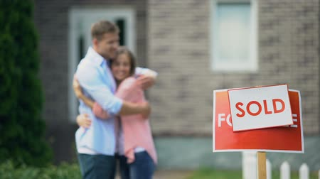 проданный : Cute couple hugging and smiling, celebrating purchase of great house, signboard