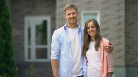 приехать : Happy couple standing against new bought house, real estate agency, property Стоковые видеозаписи