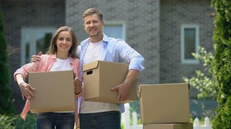 credit : Young family with cardboard boxes looking at camera, moving to new house, credit Stock Footage