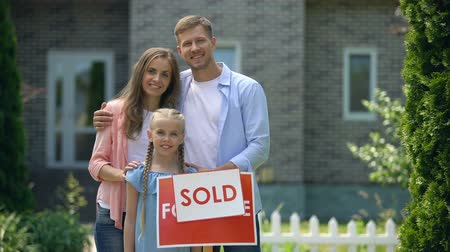 проданный : Happy family holding sold sign, standing against new bought house, thumbs up