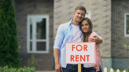 для продажи : Happy couple hugging near for rent signboard, family renting out summer house