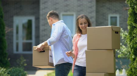 проданный : Family moving to new house, husband carrying heavy cardboard boxes, rental