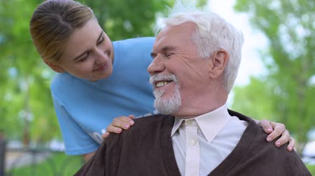 nursing : Smiling social worker taking care of aged pensioner, nursing home volunteering Stock Footage