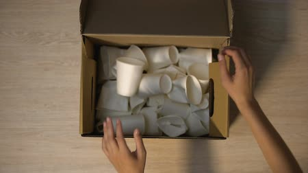 reciclado : Lady hands putting disposable cups in cardboard box with word Cellulose written Stock Footage