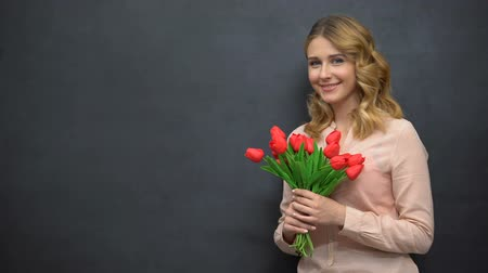 övgü : Young woman with flowers standing near blackboard, celebrating teachers day