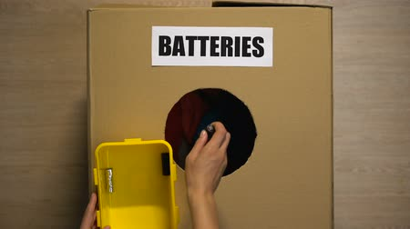 барахло : Female throwing used batteries in box for recycling, heavy metals disposing