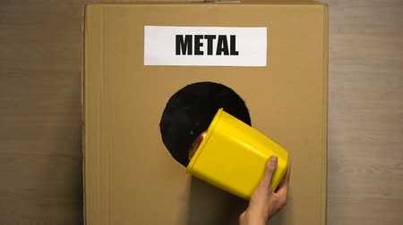 分離 : Metal word written on cardboard box, female throwing aluminum cans for reuse