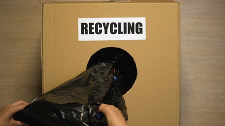 escrito : Recycling written on box, female hand putting plastic bottles inside, utilize