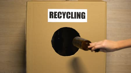 poluir : Recycling word written on cardboard box, people hands throwing reusable trash Stock Footage