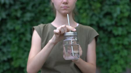 reutilizável : Woman drinking water from glass mug, choosing reusable safe materials, ecology
