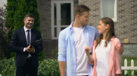 satılır : Estate broker watching happy couple enjoying new house showing keys to camera Stok Video