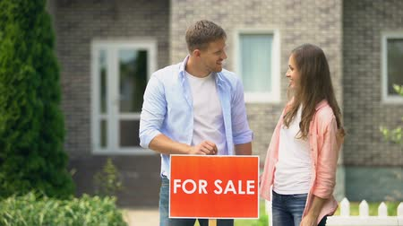human interest : Attractive couple hugging installing for sale signboard in front of house, life
