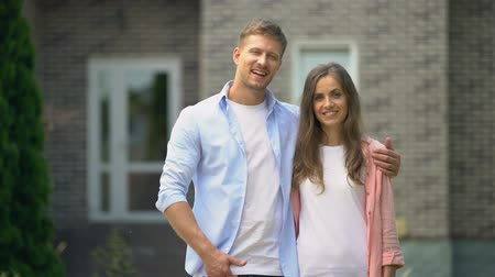 polegar : Smiling couple showing thumbs up, standing against house, real estate purchase