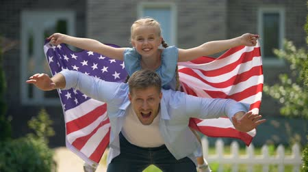 bandeira americana : Father and daughter fooling around, girl waving USA flag, independence day