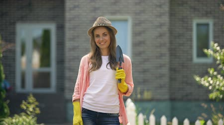 sprzątanie : Beautiful female showing hand shovel, smiling at camera, gardening hobby concept