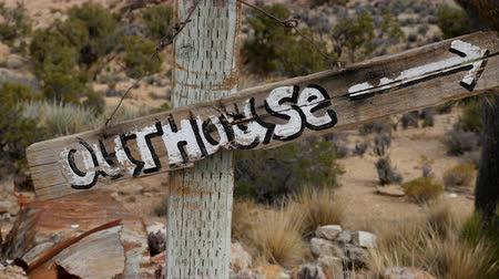 Gros plan de Outhouse Sign soufflant dans le vent - Mojave Desert - Riley's Camp