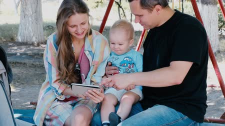 Happy young parents and their little son looking at photos on the smartphone Wideo